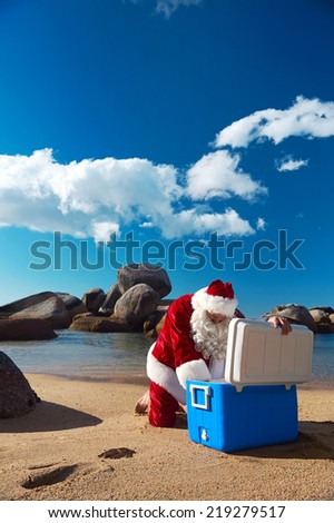 Father Christmas taking something out of his Cooler while relaxing on the beach on holiday - stock photo