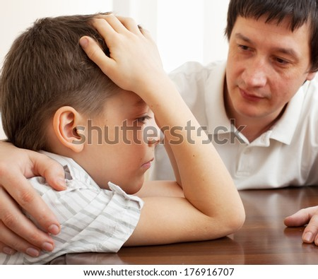 Father comforts a sad child. Problems in the family - stock photo