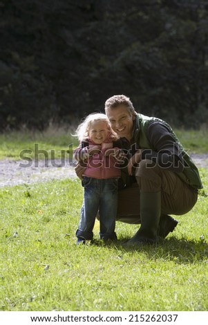 Father crouching beside daughter on grass in park, smiling, portrait - stock photo