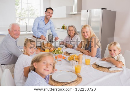 Father cutting turkey and looking at camera for thanksgiving - stock photo