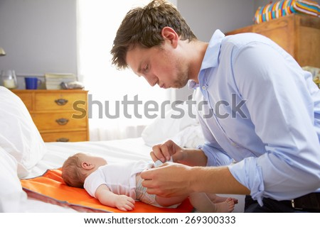 Father Dressed For Work Changing Baby's Diaper In Bedroom - stock photo