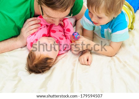 father enjoying time together with little son and newborn daughter - stock photo