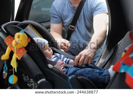 Father fasten his little son in car seat - stock photo