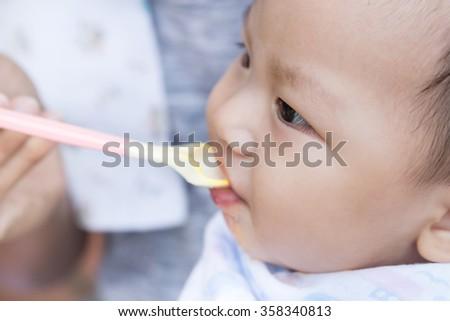 Father feeding baby food to cute newborn baby  - stock photo