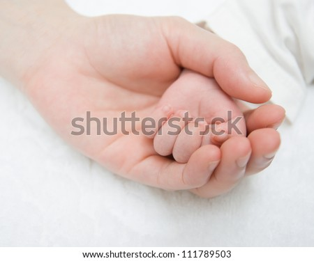 father gently hold a newborn baby's hand - stock photo