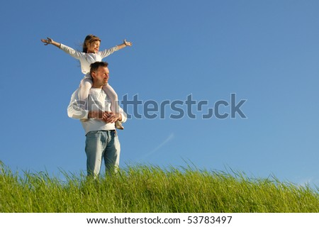 Father gives her daughter piggyback - stock photo