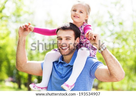 Father Giving Daughter Piggyback Ride  - stock photo