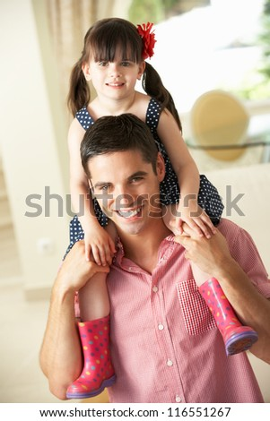 Father Giving Daughter Ride On Shoulders Indoors - stock photo