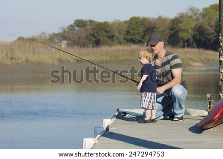father giving fishing instructions to young son or grandson - stock photo