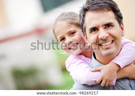 Father giving her daughter a piggyback ride - stock photo