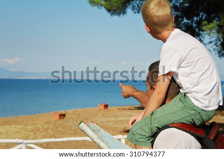 Father giving his son piggyback ride outdoors. Man and boy son looking at map in front of sea, pointing away, active summer holiday vacation, family travel photo - stock photo