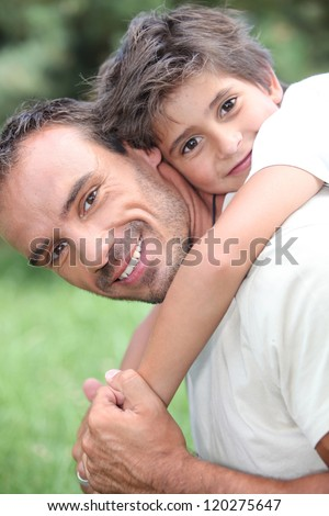 Father giving son piggy back outdoors - stock photo