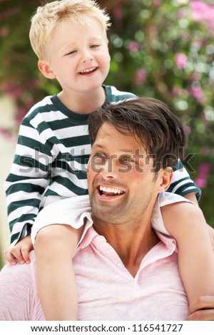 Father Giving Son Ride On Shoulders Outdoors - stock photo