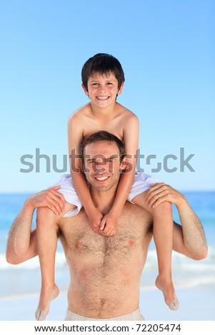 Father having son a piggyback on the beach - stock photo
