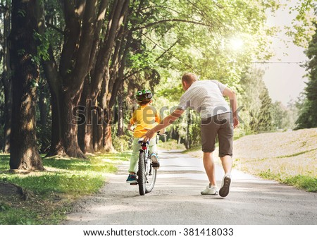 Father help his son ride a bicycle - stock photo