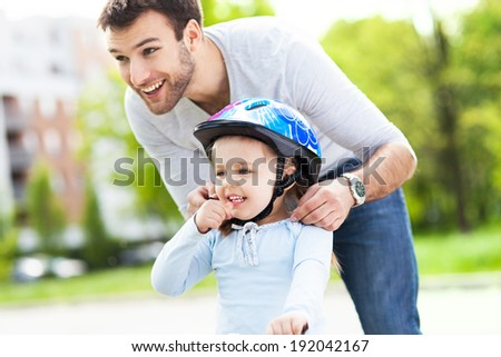 Father helping daughter with bike helmet  - stock photo