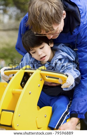 Father helping disabled son play on playground equipment - stock photo