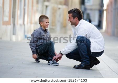 Father helping her son to tie his shoes - stock photo