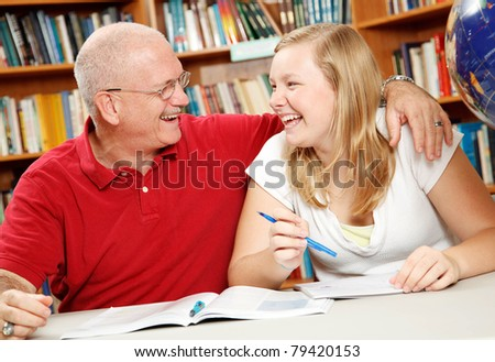 Father helping his daughter do homework, in the library. - stock photo