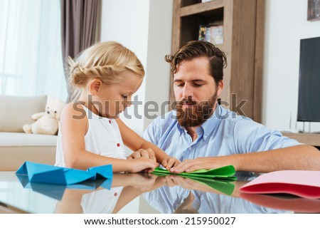 Father helping his daughter to make paper plane - stock photo