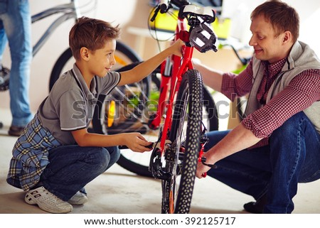 Father helping his son fix a bicycle - stock photo