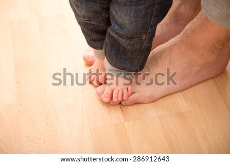 Father helping his son for the first steps. - stock photo