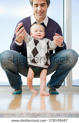 father helping his son walk - stock photo