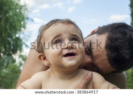 Father holding and kissing his little baby in the field in a clear day. - stock photo