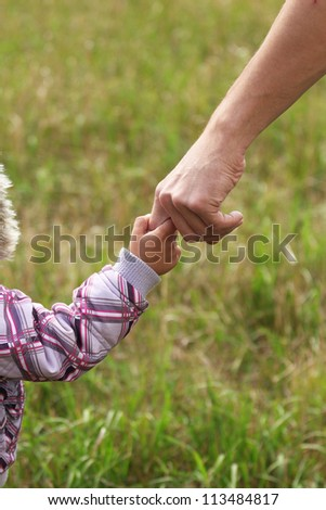 Father holding baby's hand - stock photo