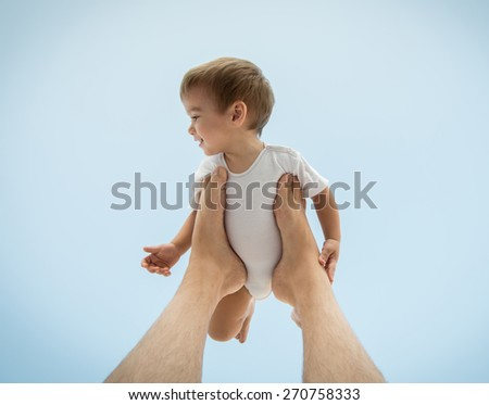 Father holding baby son on his legs in air - stock photo