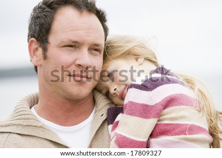 Father holding daughter at beach - stock photo