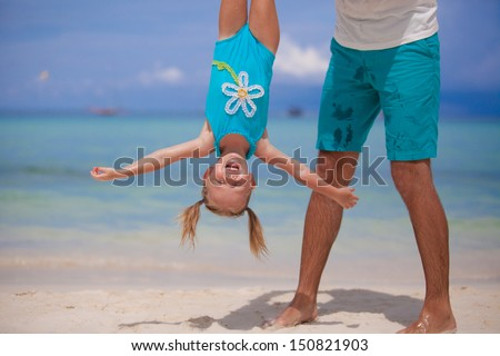 Father holding his happy smiling daughter upside down on sandy beach - stock photo