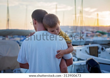 Father, holding his young child, while sleeping, enjoying the sunset over a harbor, France - stock photo