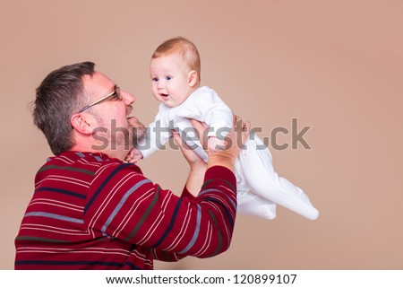 Father holding little boy in hands - stock photo