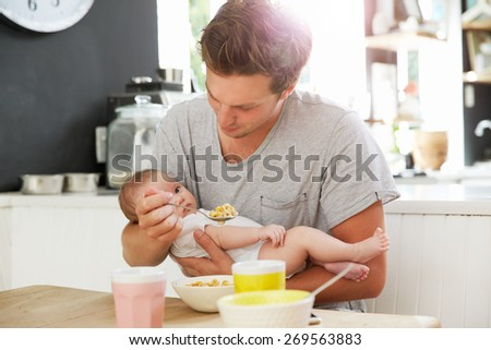 Father Holding Newborn Baby Daughter At Kitchen Table - stock photo