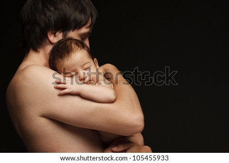 Father holding newborn baby over black background - stock photo