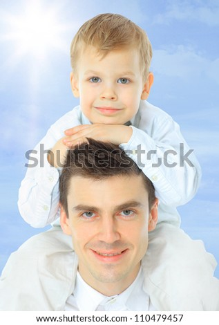 Father holding son on his shoulders - stock photo