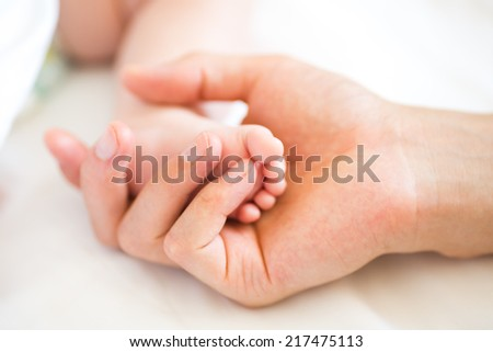 Father holding the foot of his new born son, shallow DOF - stock photo