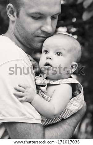 Father holds baby son in her arms in the open air ( black and white ) - stock photo