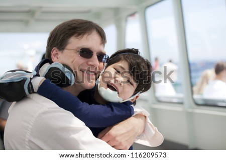 Father hugging disabled son as they ride a ferry boat - stock photo