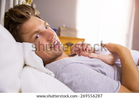Father In Bed Holding Sleeping Newborn Baby Daughter - stock photo