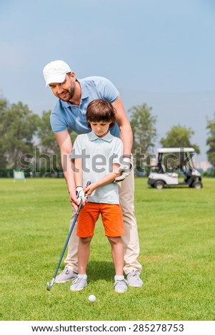 Father is always near to help me. Joyful young manteaching his son to play golf while standing on the golf course - stock photo