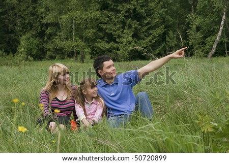 Father is pointing out something to his family while resting outdoor. Woman, man and child are resting outdoor. - stock photo