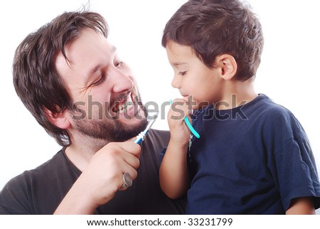 Father is teaching his son hot to clean the teeth properly - stock photo
