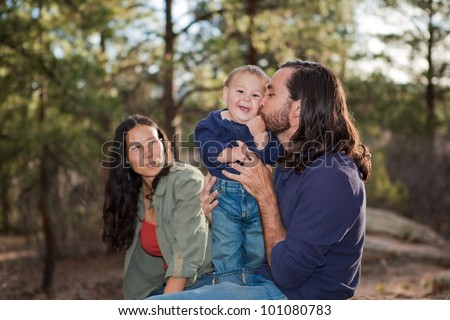 Father kissing baby boy, mother sitting in the background. Shallow DOF, focus on baby. - stock photo