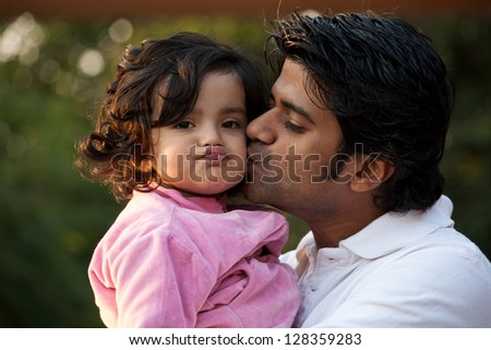 father kissing his daughter, indian man with his one year old daughter - stock photo