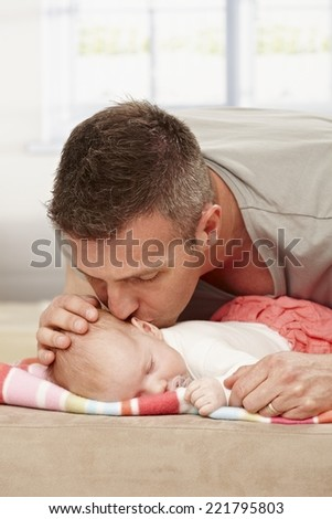 Father kissing sleeping baby tenderly. - stock photo