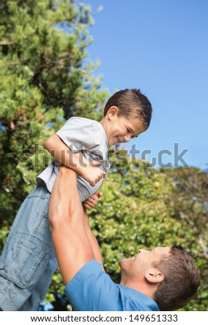 Father lifting up his son on a beautiful day in the park - stock photo