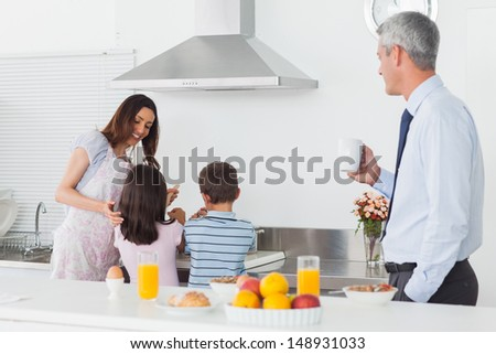Father looking at his family cooking in the kitchen before work in the morning - stock photo