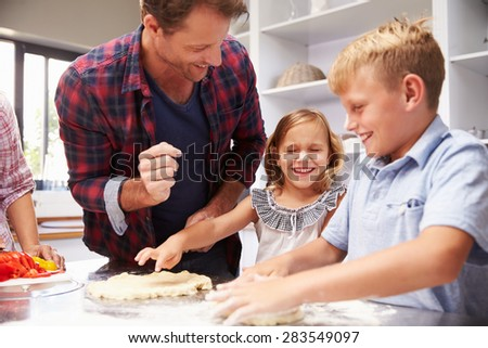 Father making pizza with kids - stock photo